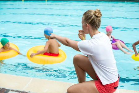 Side view of female lifeguard whistling while instructing children in swimming pool Stock Photo - 75347775