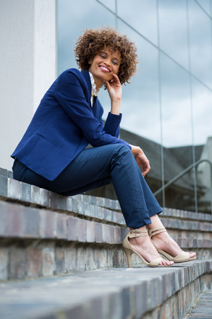 Smiling businesswoman sitting in the office premises Stock Photo