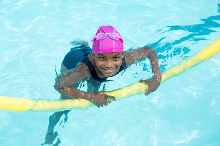 Hoge hoek weergave van meisje zwemmen met pool noodle Stockfoto
