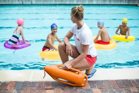 女性ライフガードの救助を保持ことができます子供のプールで水泳を中 写真素材