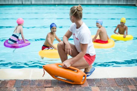 Female lifeguard holding rescue can while children swimming in pool Reklamní fotografie - 75347782