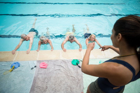 High angle view of young trainer assisting senior swimmers at poolside Stock Photo - 75347798
