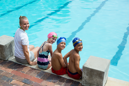 Portrait of cheerful swimming instructor and students at pool side