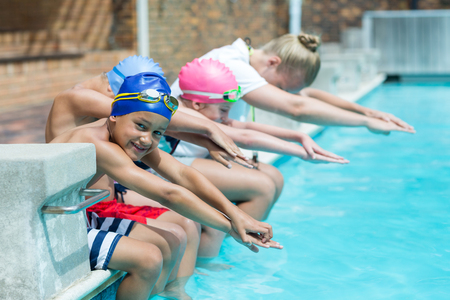 Female swimming trainer teaching children at pool side Stock Photo