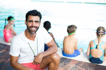 Portrait of happy male instructor crouching by children at poolside