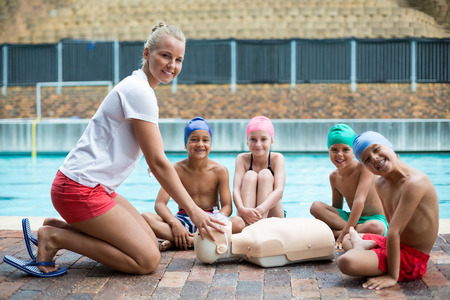 Portrait of children and instructor during rescue training at poolside Stock Photo
