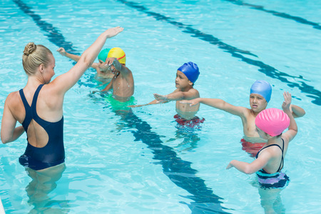 niño sin camisa: Female trainer instructing students in swimming pool