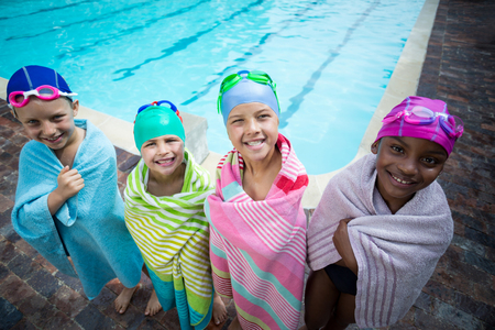Portrait of little swimmers wrapped in towels standing at poolside