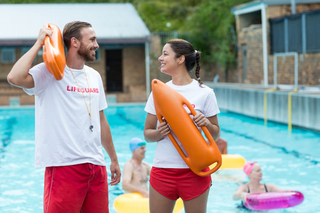 western script: Male and female lifeguards holding rescue cans at poolside