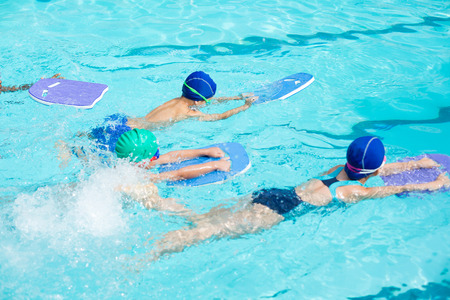 High angle view of little swimmers with kickboards swimming in pool