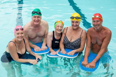 Vysoký úhel pohledu senior plavci představují s kickboards v bazénu