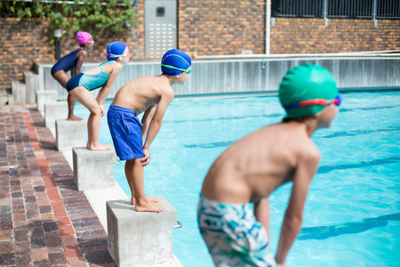 Little swimmers waiting on stating blocks at poolside Stock Photo