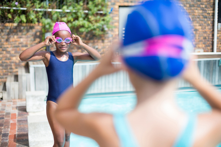 Little girls wearing swimming goggles at poolside