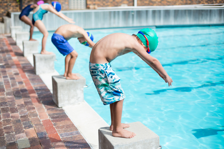Row of little swimmers ready to jump in pool Stock Photo