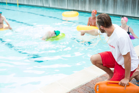 Male lifeguard assisting swimmers at poolside