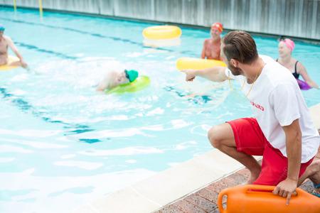 Mannelijke badmeester bijstaan ??bij zwemmers bij het zwembad Stockfoto - 75351242