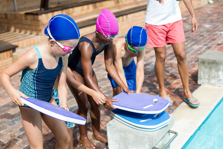 Low section of lifeguard assisting children for arranging kickboards at poolside Stock Photo