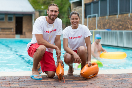Portrait of male and female lifeguards holding rescue cans at poolside