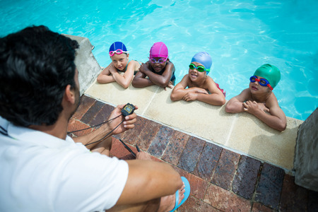 High angle view of male instructor using stopwatch while training little swimmers at poolside