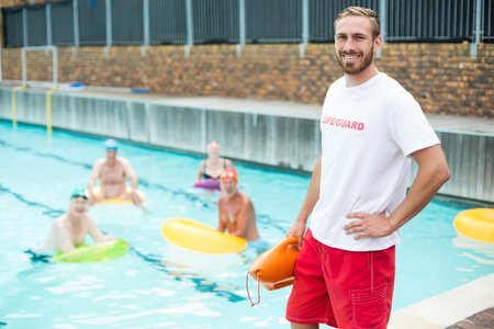 Portrait of male lifeguard standing while swimmers swimming in pool