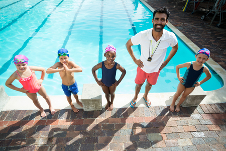 Portrait of male instructor with children at poolside
