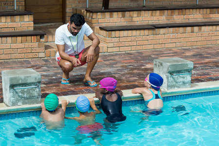 Male instructor advising little swimmers at poolside