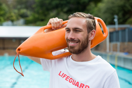 western script: Close up of smiling male lifeguard carrying rescue can at poolside