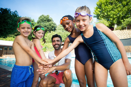Portrait of male instructor and children stacking hands at poolside