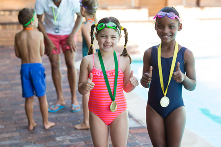 Portrait of little girls showing thumbs up while wearing medals at poolside Reklamní fotografie - 75351297