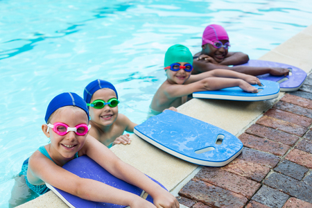 Portrait of little swimmers with kickboards leaning at poolside