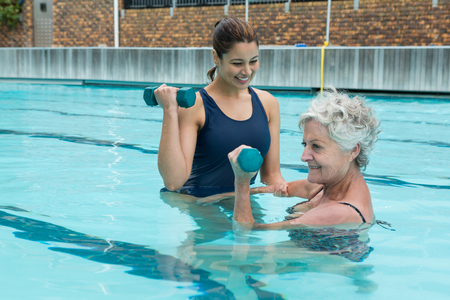 Female coach assisting senior woman in lifting dumbbells in swimming pool Stock Photo