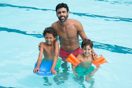 Portrait of father and kids smiling in the pool Stock Photo