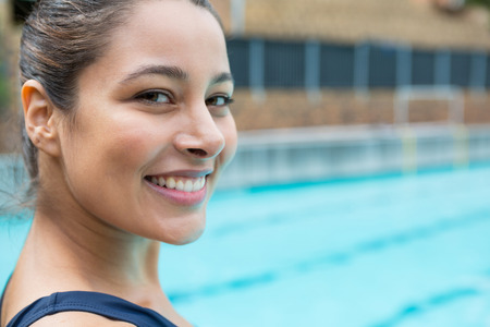 Portrait of female swimmer smiling at poolside