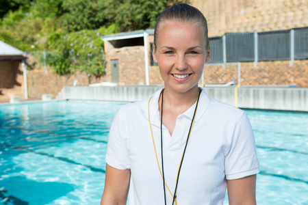 on duty: Portrait of smiling female coach standing near poolside at the leisure center