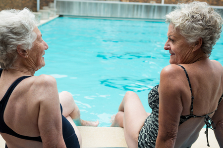 Senior women interacting with each other while relaxing at poolside
