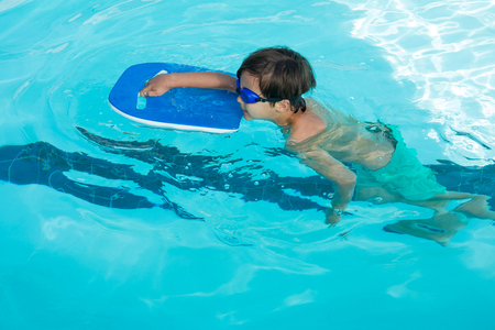 chest compression: Boy swimming in the pool on a sunny day Stock Photo