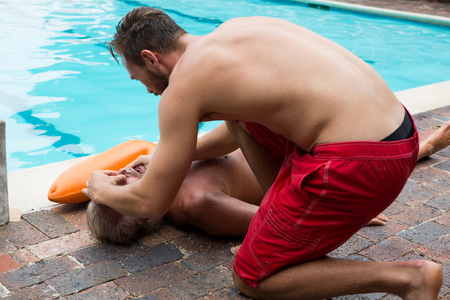 chest compression: Lifeguard helping unconscious senior man at poolside