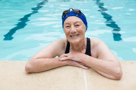 Portrait of smiling senior woman standing in swimming pool