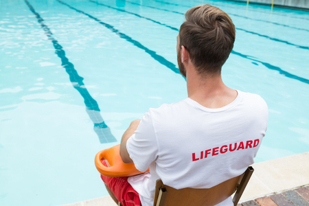 Rear view of lifeguard sitting on chair with rescue buoy at poolside