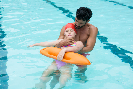 Lifeguard rescuing unconscious girl from swimming pool