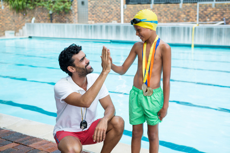 Boy giving high five to coach near poolside at the leisure center Stock Photo