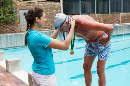 Female coach giving gold medal to senior man at poolside