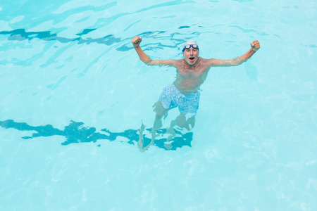 Portrait of excited senior man standing in swimming pool