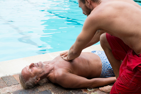 chest compression: Lifeguard pressing chest of unconscious senior man at poolside