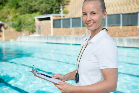 Portrait of smiling swim coach holding clipboard at poolside Stock Photo