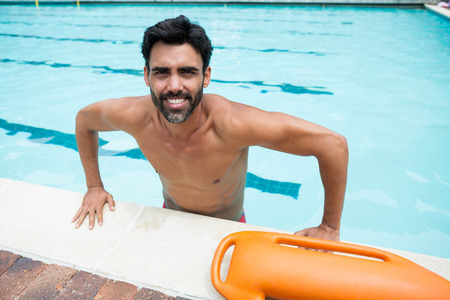 Portrait of smiling man standing in swimming pool Stock Photo