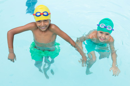 Portrait of two smiling kids swimming in the pool at the leisure center