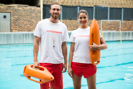 Portrait of two lifeguards standing with rescue buoy at poolside