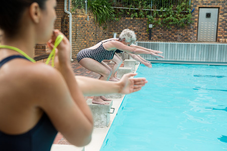 Female trainer whistling while senior women diving into pool at the leisure center