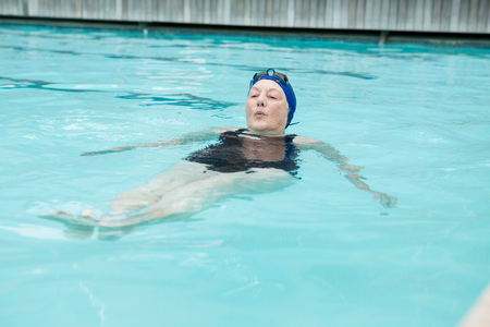 Senior woman swimming in pool at the leisure center